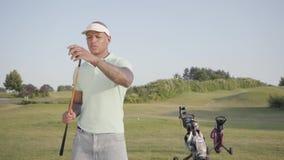 Homem do Oriente Médio bem sucedido seguro do retrato com um clube de golfe que está em um campo de golfe no bom tempo ensolarado filme