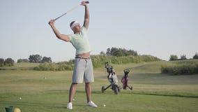 Homem do Oriente Médio do retrato que aquece-se antes do jogo, guardando um clube de golfe sobre sua cabeça Lazer do ver?o vídeos de arquivo