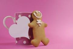 Homem do pão do gengibre do Feliz Natal com a xícara de café cor-de-rosa do às bolinhas Imagem de Stock Royalty Free