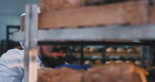 Homem do padeiro da indústria de padaria carismático com a barba que cheira com prazer o pão cozido fresco e para tomar algum pão filme