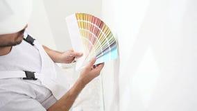 Homem do pintor no trabalho com as amostras das amostras de folha da cor, conceito da pintura de parede, espaço branco da cópia filme