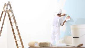 Homem do pintor no trabalho com as amostras das amostras de folha da cor, o conceito da pintura de parede, a escada no fundo e na video estoque