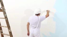 Homem do pintor no trabalho com escova, conceito da pintura de parede, fundo branco filme
