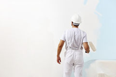 Homem do pintor no trabalho com um rolo de pintura, pintura de parede Fotos de Stock Royalty Free