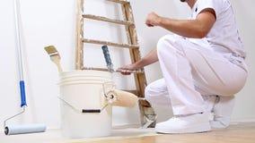 Homem do pintor no trabalho com um rolo, uma cubeta e uma escada video estoque