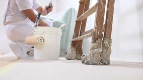 Homem do pintor no trabalho, restos o rolo de pintura na cubeta video estoque