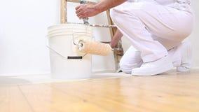Homem do pintor no trabalho, restos o rolo de pintura na cubeta filme