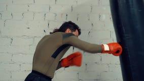 Homem do pugilista nas luvas que treina o pontapé pelo saco do encaixotamento no fundo branco da parede de tijolo video estoque