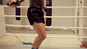 Homem do pugilista que salta na corda de salto quando cardio- treinamento no anel no clube da luta Kickboxer que faz o salto para vídeos de arquivo