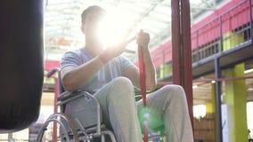 Homem do retrato com uma inabilidade em fitas de um encaixotamento da ferida da cadeira de rodas em suas mãos video estoque
