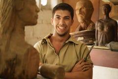 Homem do retrato que trabalha a escultura de madeira da arte feliz do artista na oficina Fotos de Stock