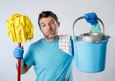 Homem do serviço doméstico ou trabalhos domésticos forçados do marido que lavam guardando o espanador e a cubeta foto de stock royalty free