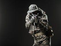 Homem do soldado das forças especiais com metralhadora em um fundo escuro Fotografia de Stock