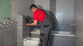 Homem do trabalhador para instalar o mecanismo do sistema de nivelamento da água de toalete filme