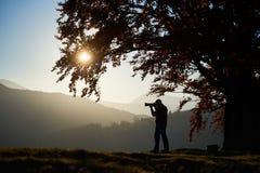 Homem do turista do caminhante com a câmera no vale gramíneo no fundo da paisagem da montanha sob a árvore grande foto de stock royalty free