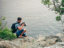 Homem do turista do fotógrafo que olha a câmera digital do profissional de SLR da tela imagens de stock