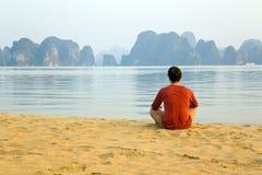 Homem do turista na praia, opinião da pedra calcária da baía do halong, Vietnam imagem de stock