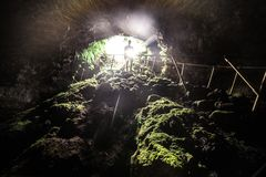 Homem do turista para explorar a caverna da lava com luz do flash em Maui, Havaí imagens de stock
