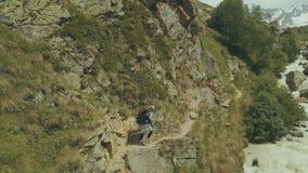 Homem do turista que anda na fuga de montanha ao longo do rio rápido video estoque