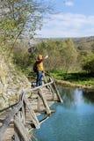 Homem do turista que está em uma ponte de madeira na montanha que toma fotos com o telefone imagem de stock royalty free