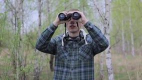 Homem do turista que olha através dos binóculos filme