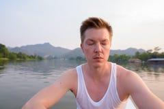 Homem do turista que senta-se no barco ao ter o feriado em Tailândia fotos de stock royalty free