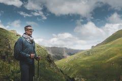 Homem do viajante com trouxa e Polos Trekking que descansam e que olham as montanhas no verão exterior fotografia de stock royalty free