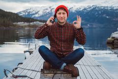Homem do viajante que fala no telefone celular Turista que senta-se no cais de madeira no fundo da montanha e do lago viajante imagens de stock