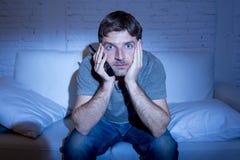 Homem do viciado da televisão em casa que encontra-se no sofá que olha a tevê guardar o controlo a distância imagens de stock