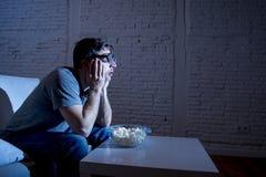 Homem do viciado da televisão no sofá que olha a tevê e que come a pipoca em vidros engraçados do totó do lerdo Foto de Stock