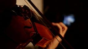 Homem do violinista que joga o violino em um fundo preto Fim acima filme
