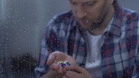 Homem doente comprimido que guarda a palma completa da medicamentação, sentando-se atrás da janela chuvosa filme