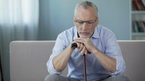 Homem doente em seu 50s que senta-se no sofá, pondo as mãos sobre a vara de passeio depression video estoque