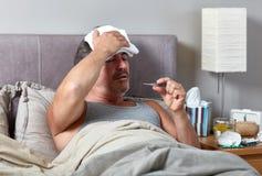 Homem doente na cama fotografia de stock