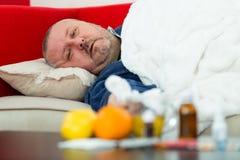 Homem doente na cama com drogas e fruto na tabela Fotos de Stock Royalty Free