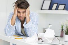 Homem doente novo que sofre da dor de cabeça no contador de cozinha Foto de Stock