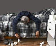 Homem doente que encontra-se através da cama Fotos de Stock Royalty Free