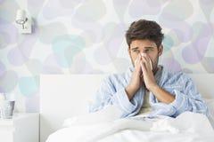 Homem doente que funde seu nariz ao sentar-se na cama em casa fotografia de stock royalty free