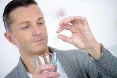 Homem doente que guarda o comprimido com água de vidro fotografia de stock