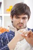 Homem doente que olha o termômetro imagens de stock