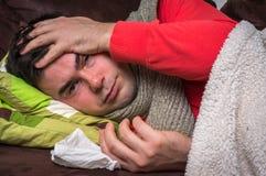 Homem doente que tem a gripe e a dor de cabeça foto de stock