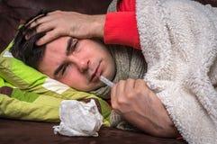 Homem doente que tem a gripe e a dor de cabeça fotografia de stock royalty free