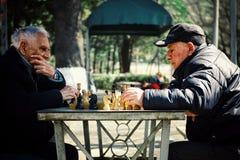 homem dois idoso superior que joga a xadrez em um parque público fotos de stock