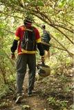 Homem dois novo que caminha na selva tropical com trouxa Caminhante masculino com mochila que anda ao longo da fuga da floresta Fotografia de Stock Royalty Free
