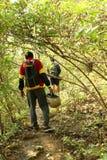 Homem dois novo que caminha na selva tropical com trouxa Caminhante masculino com mochila que anda ao longo da fuga da floresta Imagens de Stock Royalty Free