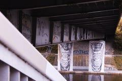 Homem dois que guarda grafittis da ponte em Vilnius fotos de stock