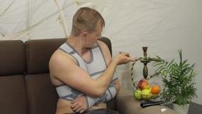 Homem doloroso com a cinta vestindo do braço do braço quebrado que faz-se picar da dor filme