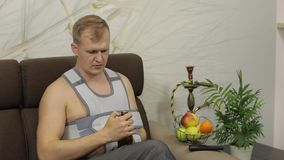 Homem doloroso com uma cinta vestindo do braço do braço quebrado que senta-se em uma cerveja das bebidas do sofá video estoque