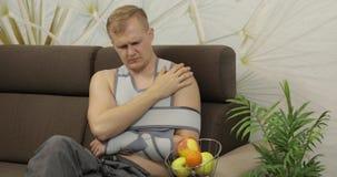 Homem doloroso com uma cinta vestindo do braço do braço quebrado que senta-se em um sofá que olha a tevê filme