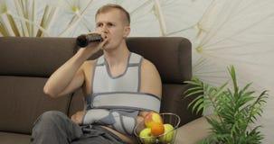 Homem doloroso com uma cinta vestindo do bra?o do bra?o quebrado que senta-se em uma cerveja das bebidas do sof? vídeos de arquivo